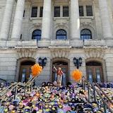En las escaleras de la Legislatura de Regina, cientos de mochilas escolares con la mano de un niño recortada en papel. Dos ramos de globos y una mujer de pie en medio de la escena.