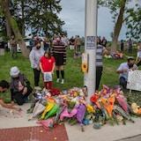 Ramos de flores junto a un poste con gente reunida en señal de duelo.