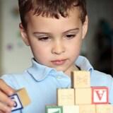 Un enfant autiste joue avec des blocs.