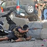 مسلّح مقنّع يحمل رشاشا يحتمي خلف جدار.