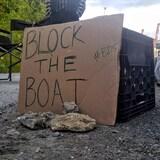 """لافتة مكتوب عليها """"امنعوا السفينة""""."""