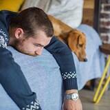 Un homme couché sur un lit déprimé et son chien est déprimé aussi