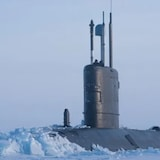 The top of a submarine is shown breaking through sea ice.