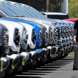 Un hombre camina en un lote de autos.