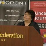 Una mujer indígena detrás de un podio