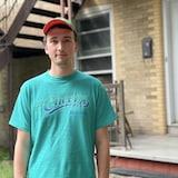 Un jeune homme portant une casquette et un chandail turquoise regarde l'objectif.