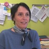 Femme portant un chandail bleu dans son bureau en entrevue.