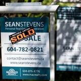 Une pancarte où il est inscrit «vendu» devant une maison.