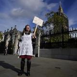 Une femme tient une pancarte devant le parlement britannique.