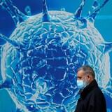 Un hombre con una máscara pasa por delante de una ilustración muy grande de un coronavirus.