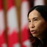 Une femme en conférence de presse devant une rangée de drapeaux du Canada.