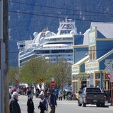 A street scene in Skagway Alaska with the silhouette of a cruise ship in the background.