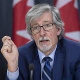 Daniel Therrien assis devant une série de drapeaux du Canada.