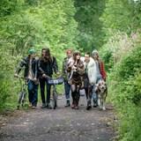 Un groupe de jeunes marchent sur un chemin avec un chien.
