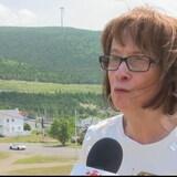 Une femme se fait interviewer à l'extérieur. Derrière elle on voit des montagnes.