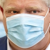 Doug Ford à un point de presse, portant un masque de type chirurgical.