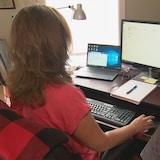 Une femme de dos est assise à un bureau. elle manipule de la main droite une souris d'ordinateur et regarde en direction des deux écrans qui sont devant elle.