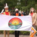 Trois personnes tiennent le drapeau dans un parc.