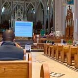 Des gens sont assis dans différentes rangées d'une église. À l'avant, une présentation Powerpoint est projetée sur une toile.