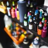 On voit en gros plan des bouteilles de plastique de différentes couleurs posées sur des étagères.