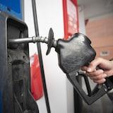 Une main tient une pompe à essence.
