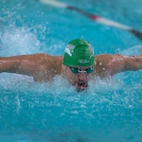 Étienne Paquin-Foisy en plein mouvement de papillon dans une piscine. Il porte un casque et des lunettes.