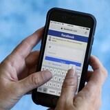 Une personne écrit un message via Facebook sur son cellulaire