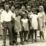 Des hommes, des femmes et des enfants posent ensemble pour une photo. Derrière eux se trouvent des arbres et des tournesols.