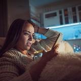 Une femme consulte son téléphone dans son lit la nuit.