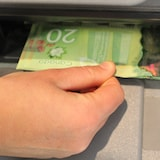 Une main retire vingt dollars d'un guichet automatique