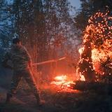 Un volontaire, pelle à la main, en train de d'éteindre le feu dans une forêt.