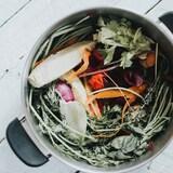 Des pelures et noyaux de légumes et fruits sont déposés dans un chaudron.
