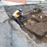 Deux personnes s'affairent sur un site archéologique au centre-ville. Des parcelles de terre sont clairement délimitées.