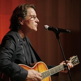 L'homme chante et joue de la guitare sur scène.