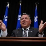 رئيس حكومة كيبيك فرانسوا لوغو متحدثاً في مؤتمر صحفي  ونراه رافعاً يديْه وأمامه ميكروفون وكوب ماء وخلفه أعلام كيبيكية.
