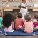 Des enfants, par terre écoutent une histoire