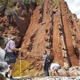 Des guides en formation devant la formation rocheuse qui montre que le terrain ea subi de puissantes transformations, passant de l'horizontale à la verticale.