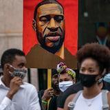 Le visage de George Floyd est dessiné sur une pancarte visible au-dessus de manifestants.