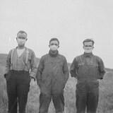 Trois hommes se tiennent debout dans un champ.