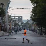 A man is crossing an empty street in Port-au-Prince.