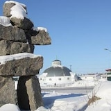 A snow-covered inukshuk in the foreground, with the Inuvik igloo church in the background.