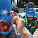 Muslim students wearing masks with the colors of the pro-independence East Turkistan flag attend a rally outside the Chinese Embassy in Jakarta, Indonesia, earlier this year. The students staged the rally to call for an end to alleged oppression against the Muslim Uyghur ethnic minority in Xinjiang.