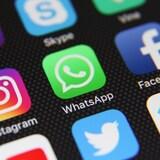 Une photo d'un écran de téléphone intelligent sur lequel sont affichés les icônes de différents réseaux sociaux. Ceux d'Instagram, de WhatsApp et de Facebook sont mis en évidence au centre.