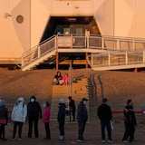 A long line up of people is shown outside of a building.