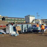 A couple carries away a package of water bottles from a distribution table manned by two workers.
