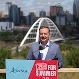 Jason Kenney en conférence de presse avec la ville d'Edmonton derrière lui.