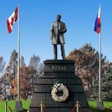 Estatwa ni Jose Rizal katabi ang mga bandila ng Canada at Pilipinas.