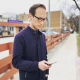 Patrick Foucault dans une rue, avec son téléphone cellulaire.