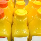 Des bouteilles de jus, en gros plan, qui sont alignées sur une tablette.