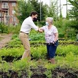Justin Trudeau salue une femme âgée du coude dans un jardin.